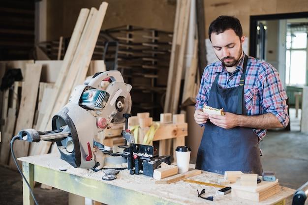 Operaio allegro di carpenteria pranzando mangiando panino in un'officina