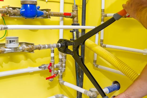Operaio che collega i tubi alupex con un rubinetto. pressa a mano per tubi dell'acqua pex - al - pe-x. industria idraulica.