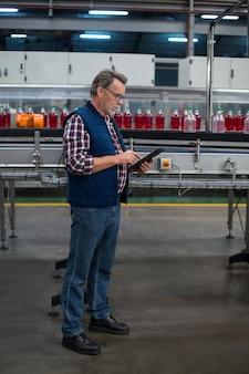 Operaio che per mezzo della compressa digitale accanto alla linea di produzione