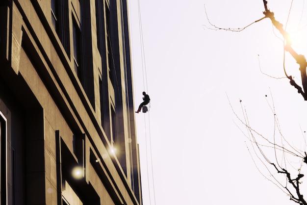 Operaio che pulisce il servizio di finestre esterne su un alto edificio