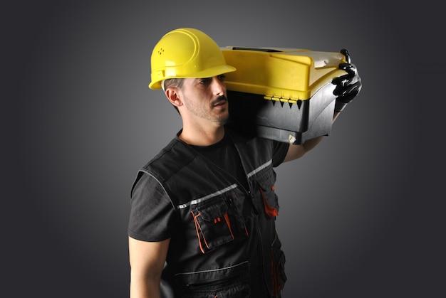 Operaio con casco giallo, trapano e martello