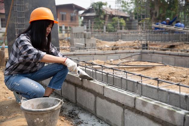 Operaio del muratore che installa la muratura del mattone sulla parete esterna con la spatola della cazzuola