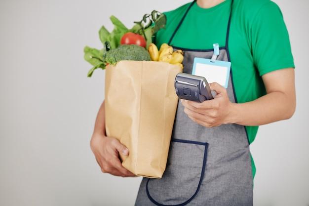 Operaio del supermercato che trasportano generi alimentari