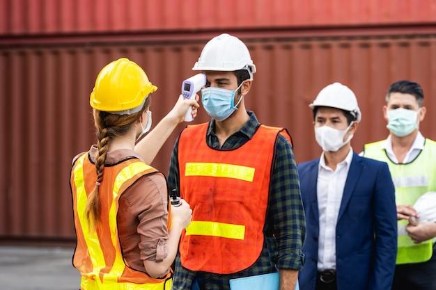Operaio dell'ingegnere che indossa mascherina chirurgica che controlla la temperatura corporea