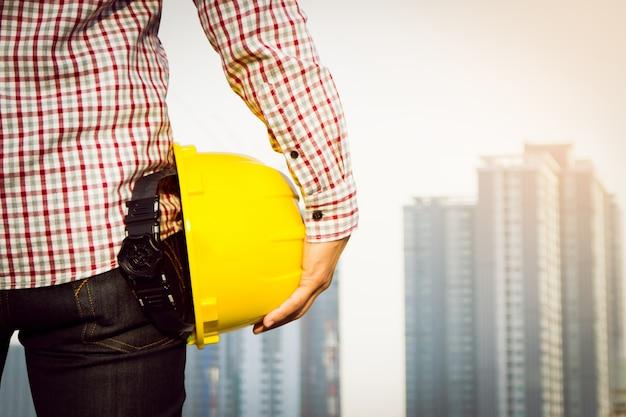 Operaio di ingegnere della mano che tiene casco di sicurezza giallo con la costruzione sullo sfondo del luogo.