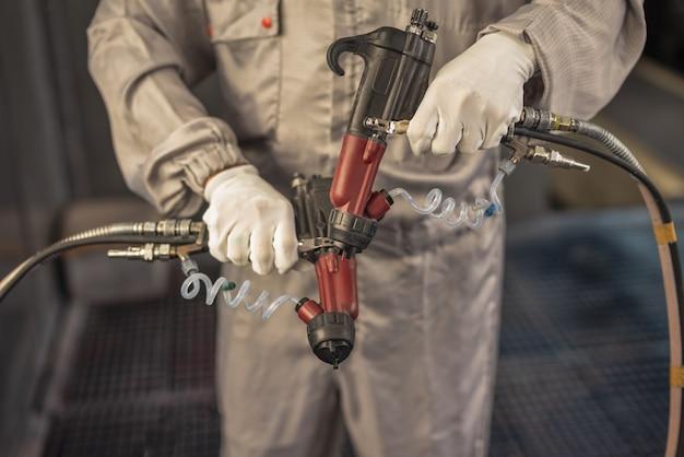 Operaio di verniciatura con spruzzatori industriali nelle sue mani