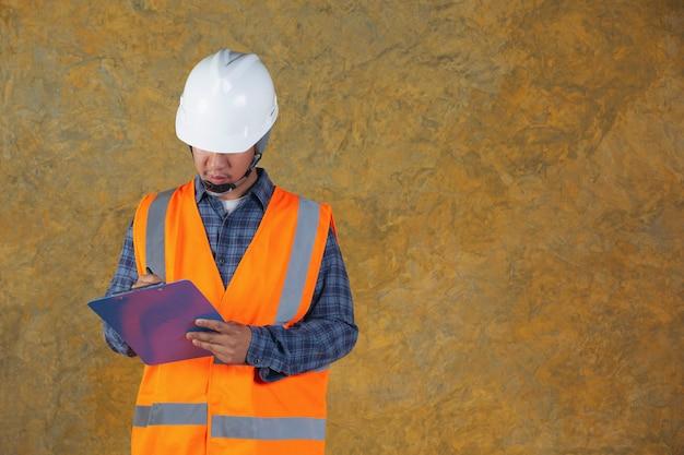 Operaio edile con documento, piano di lavoro per il cantiere interno.