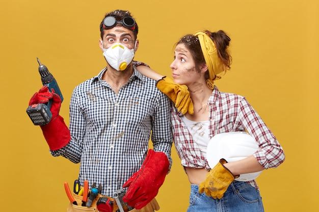 Operaio edile in maschera protettiva che indossa camicia e guanti rossi che tengono trapano in piedi vicino al suo collega che lo guarda con grande simpatia. persone, costruzione, concetto di edificio