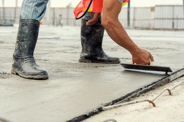 Operaio muratore che livella calcestruzzo con le mani del muratore delle cazzuole che spargono calcestruzzo versato