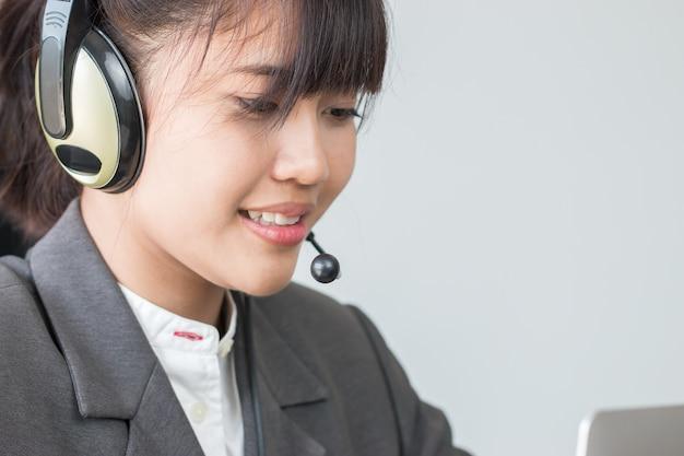 Operatore amichevole della giovane donna asiatica o agente di call center con la call center di lavoro delle cuffie avricolari