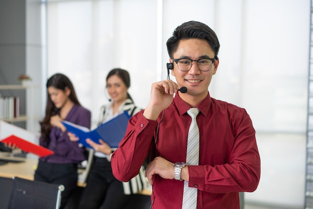 Operatore bello sorridente del servizio clienti con la cuffia avricolare che funziona nella call center