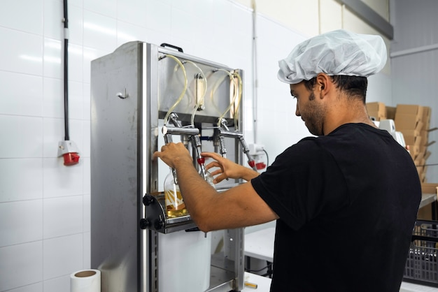 Operatore che imbottiglia manualmente nel processo di produzione kombucha in una fabbrica