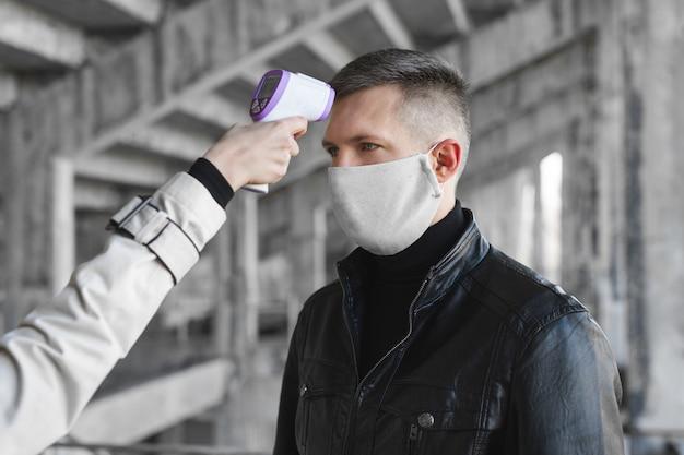 Operatore controlla la febbre dal visitatore del termometro digitale al banco informazioni per la scansione e la protezione dal coronavirus covid-19