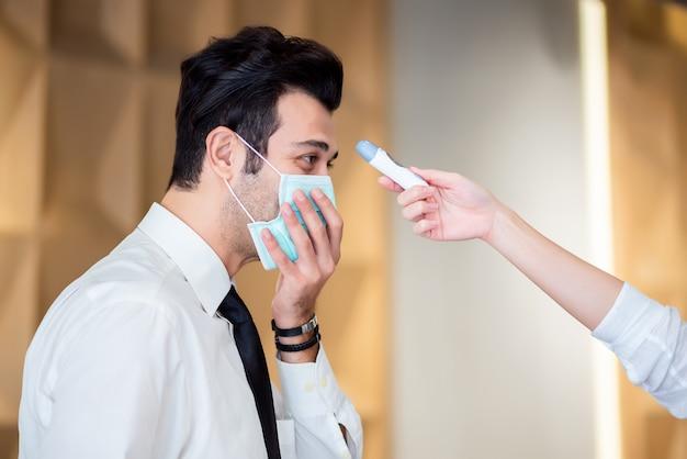 Operatore controlla la febbre dal visitatore del termometro digitale presso il banco informazioni per la scansione e la protezione da coronavirus covid-19