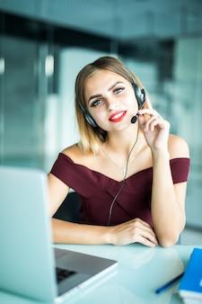Operatore del centro di supporto donna graziosa con auricolare in ufficio