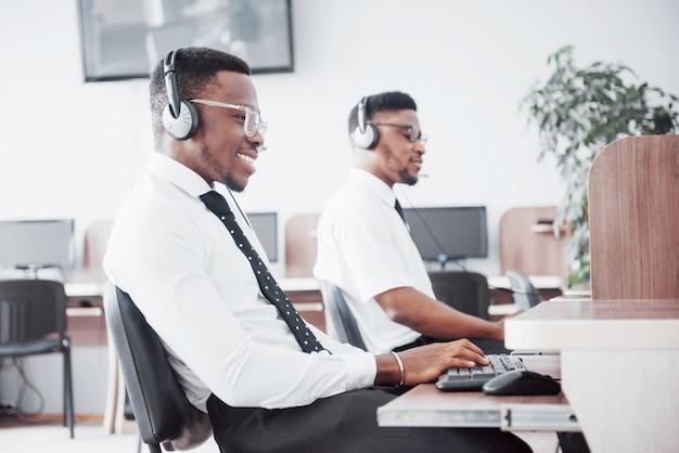 Operatore del servizio clienti afroamericano con cuffia avricolare a mani libere che lavora nell'ufficio