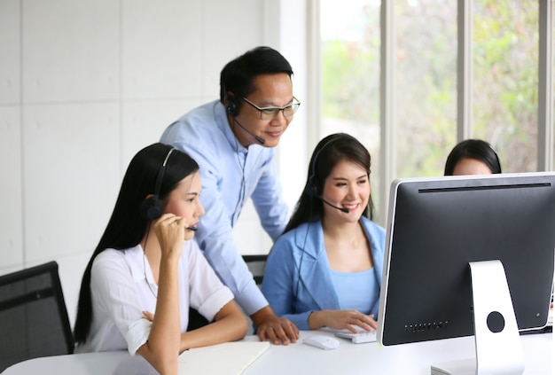 Operatore del supporto tecnico con cuffia che lavora su laptop e computer