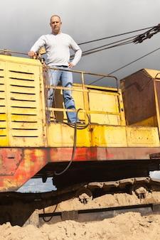 Operatore del trattore al pozzo di sabbia
