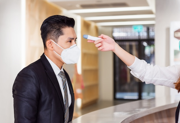 Operatore della reception che controlla febbre tramite termometro digitale per la scansione della febbre