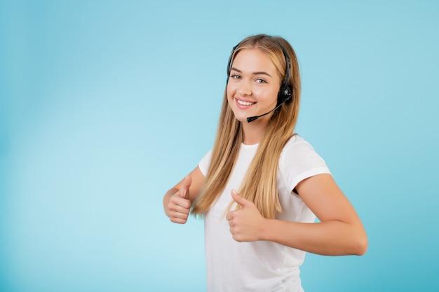 Operatore di call center biondo sorridente amichevole con la cuffia avricolare isolata sopra il blu