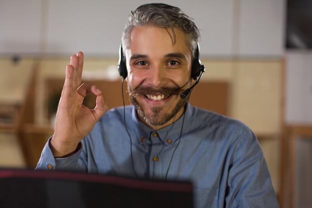 Operatore di call center felice che esamina macchina fotografica e che mostra segno giusto