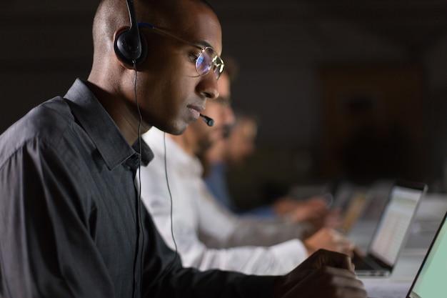 Operatore di call center messo a fuoco che scrive sul computer portatile