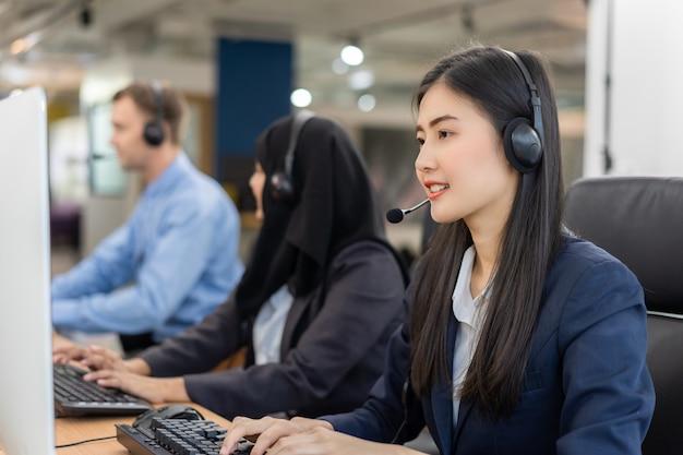 Operatore di servizio clienti donna asiatica operatore sorridente felice con cuffie lavorando sul computer in un call center, parlando con il cliente per aiutare a risolvere il problema con la sua mente di servizio