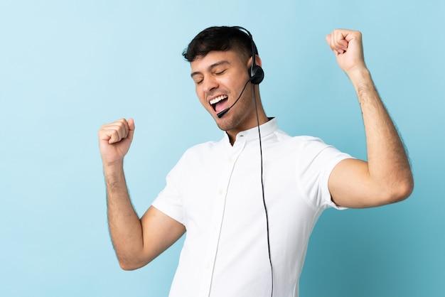 Operatore di telemarketer colombiano uomo che lavora con un auricolare isolato per celebrare una vittoria