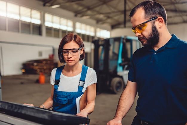 Operatore femminile cnc che controlla il codice del programma con supervisore