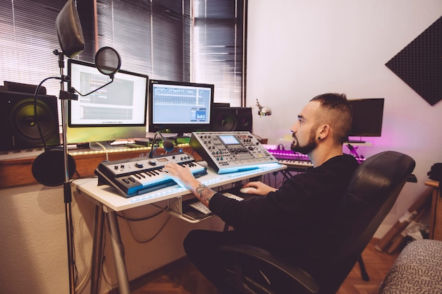 Operatore professionista di tastiera che mescola le tracce in un programma di editing audio