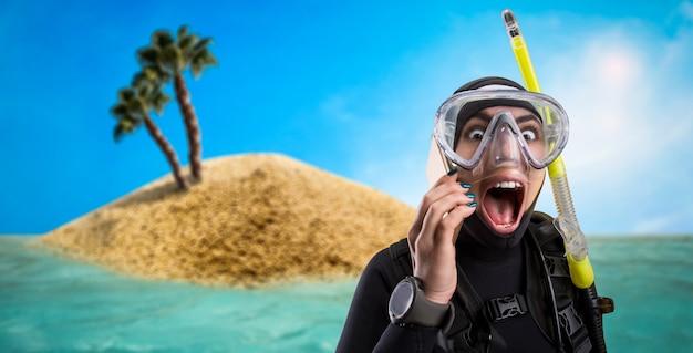 Operatore subacqueo femminile in muta e attrezzatura subacquea, isola deserta sullo sfondo. frogman in maschera e scuba, sport subacqueo