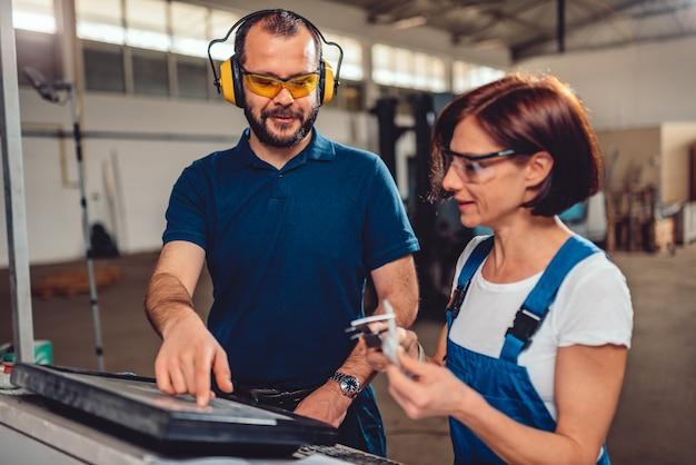Operatori di macchine a controllo numerico che lavorano nel capannone industriale