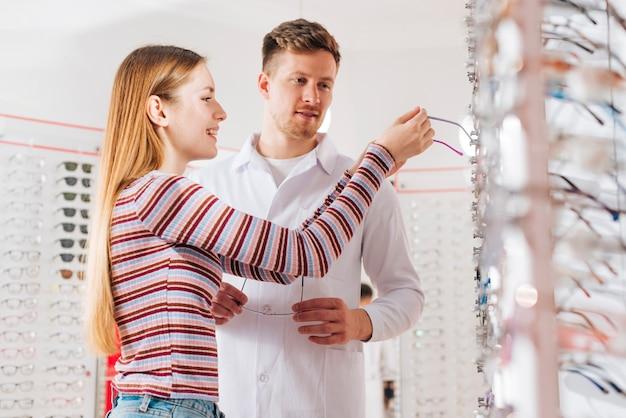 Optometrista che consiglia donna che sceglie i vetri