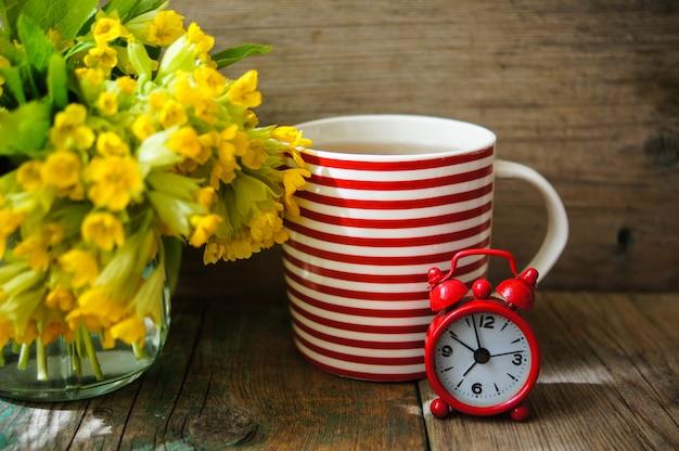 Ora di colazione con una tazza di tè e un orologio