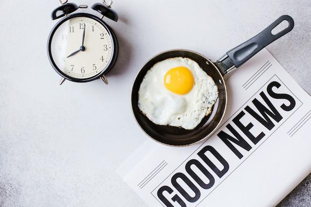 Ora di colazione. uova fritte in padella con una sveglia e un giornale su un tavolo grigio chiaro con uno sfondo a trama.