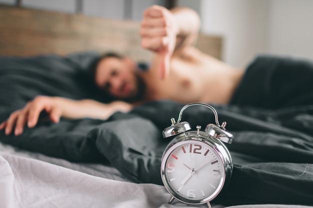 Ora di svegliarsi. uomo stanco nel letto non felice. sveglia matura della tenuta del tipo mentre controllando tempo per lavoro
