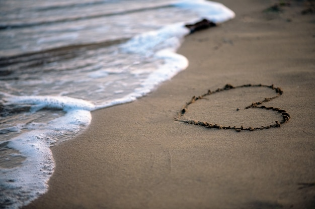 Ora legale, cuore dipinto sulla sabbia dal mare
