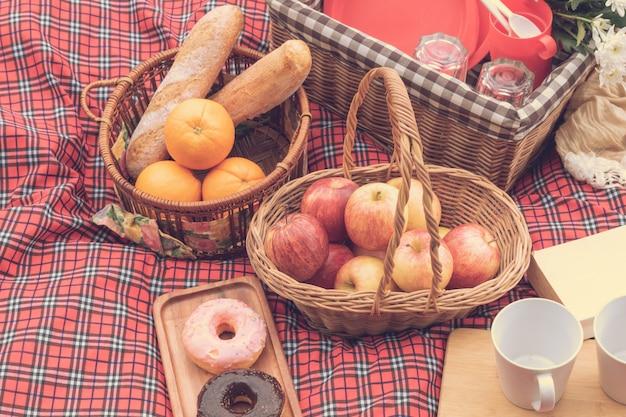 Ora legale primo piano del cestino da picnic con cibo e frutta in natura.