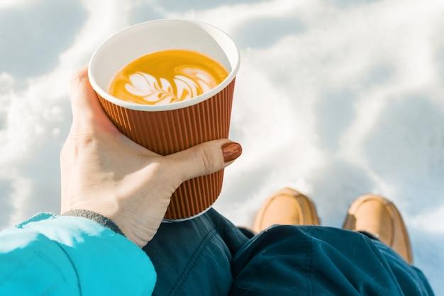 Orario invernale all'aperto, mani della donna con una tazza di caffè