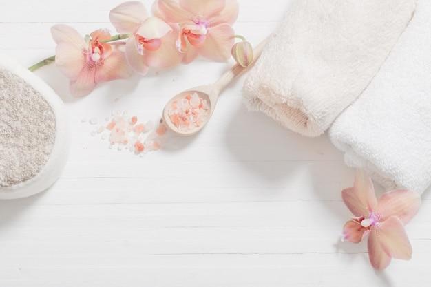 Orchidea con asciugamani su superficie di legno bianco