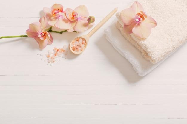 Orchidea con gli asciugamani su fondo di legno bianco