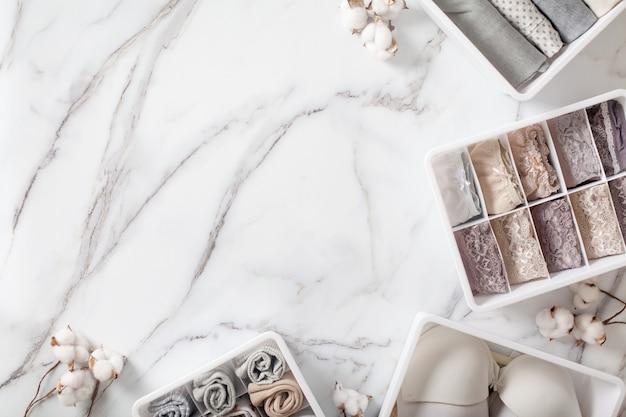 Ordinatamente e ordinato biancheria piegata nel divisore del cassetto organizer su sfondo di marmo bianco