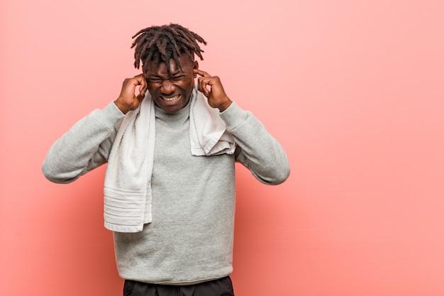 Orecchie africane della copertura dell'uomo di colore di giovane forma fisica con le sue mani.