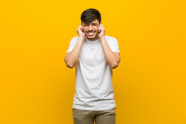 Orecchie casuali ispaniche della copertura del giovane uomo con le mani.