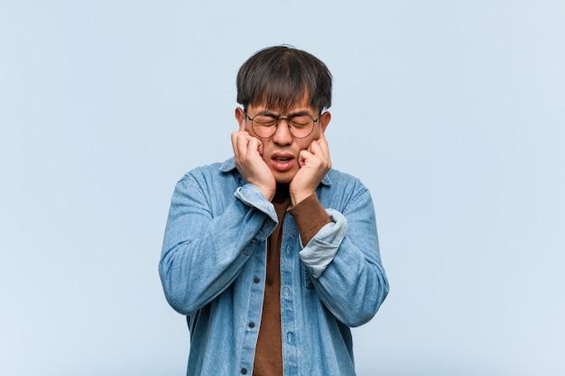 Orecchie cinesi giovani della copertura dell'uomo con le mani