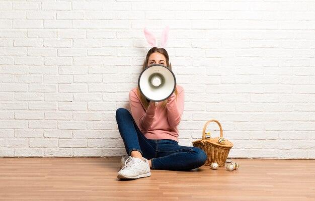Orecchie d'uso del coniglietto della giovane donna per le vacanze di pasqua che tengono un megafono