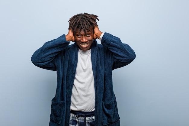 Orecchie d'uso della copertura del pigiama del giovane uomo di colore africano con le mani che provano a non sentire il suono troppo forte.