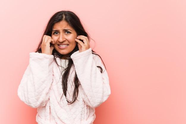 Orecchie d'uso della copertura del pigiama della giovane donna indiana con le sue mani.