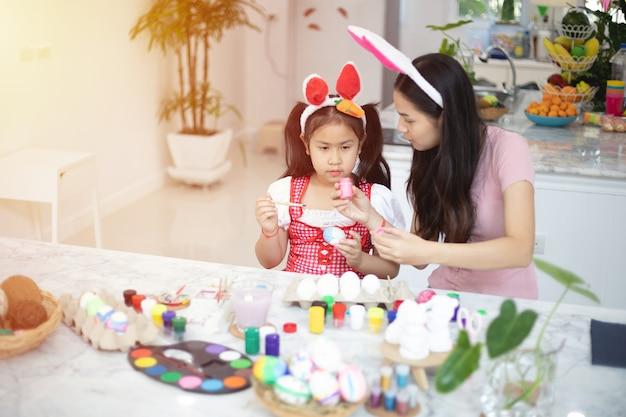 Orecchie da portare del coniglietto della piccola ragazza asiatica sveglia del bambino il giorno di pasqua.