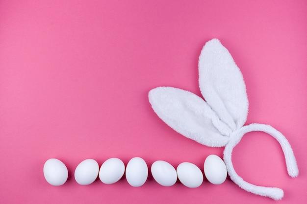 Orecchie del coniglietto con le uova bianche su fondo rosa